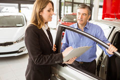 Smiling businessman undersign a car contract Royalty Free Stock Photography