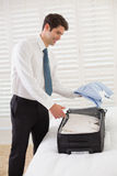 Smiling businessman unpacking luggage at a hotel bedroom Royalty Free Stock Image