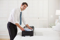 Smiling businessman unpacking luggage at a hotel bedroom Royalty Free Stock Images