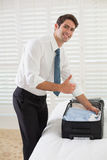 Smiling businessman unpacking luggage at a hotel bedroom Stock Photo