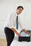 Smiling businessman unpacking luggage at a hotel bedroom Stock Image