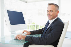 A smiling businessman uses his computer Stock Images