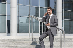 Smiling businessman using cell phone while standing on steps outside office Royalty Free Stock Images