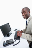A smiling businessman using a computer Stock Images