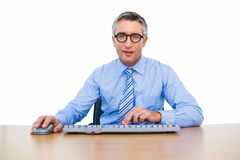 Smiling businessman using computing mouse and keyboard Stock Image