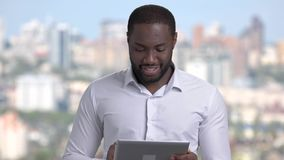 Smiling businessman using digital tablet. Handsome afro-american executive in white shirt working on cmputer tablet and smiling on blurred background stock video