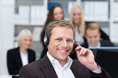 Smiling businessman using a headset. Smiling handsome young businessman using a headset in the office to facilitate hands free communication or answering calls Stock Image