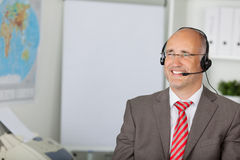 Smiling businessman using headset Stock Image