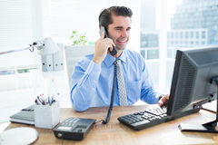 Smiling businessman using his computer ans phoning Royalty Free Stock Images