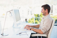 Smiling businessman using his computer at his desk Royalty Free Stock Images