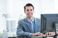 Smiling businessman using his computer Royalty Free Stock Photos