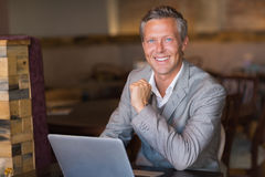 Smiling businessman using his laptop Stock Images
