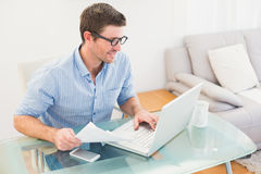 Smiling businessman using his laptop at desk Stock Photography
