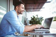 Smiling businessman using his laptop Stock Photo