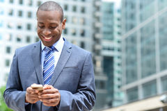 Smiling businessman using his smartphone Royalty Free Stock Photos