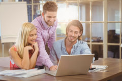 Smiling businessman using laptop while colleagues Stock Photography