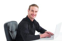 Smiling businessman using laptop at desk Stock Photos