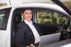 Smiling businessman using laptop in his car Royalty Free Stock Image
