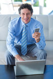 Smiling businessman using laptop and mobile phone on couch Royalty Free Stock Image