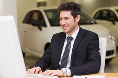 Smiling businessman using a laptop. At new car showroom Stock Photos