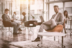 Smiling businessman using laptop in office. Portrait of smiling businessman with colleagues using laptop in office Royalty Free Stock Photos