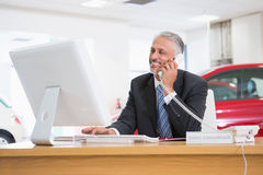 Smiling businessman using laptop on the phone Stock Image