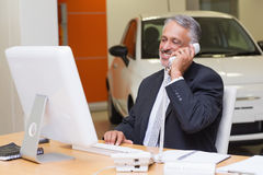 Smiling businessman using laptop on the phone Royalty Free Stock Images