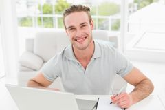 Smiling businessman using laptop and taking notes Stock Photo