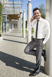 Smiling businessman using mobile phone while leaning on column outside office Royalty Free Stock Photos