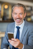 Smiling businessman using mobile phone Royalty Free Stock Images