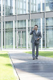 Smiling businessman using mobile phone while walking on path outside office Royalty Free Stock Image