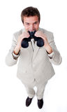Smiling businessman using a pair of binoculars Royalty Free Stock Image