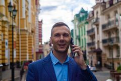 Smiling businessman using phone in city. stock photography