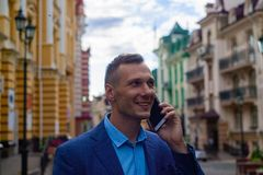 Smiling businessman using phone in city. stock images