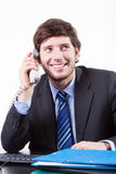 Smiling businessman using phone in office royalty free stock image