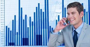 Smiling businessman using smart phone against graphs. Digital composite of Smiling businessman using smart phone against graphs Stock Photos