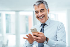 Smiling businessman using a smart phone Royalty Free Stock Image
