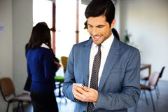 Smiling businessman using smartphone Stock Image