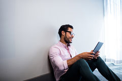 Smiling businessman using tablet computer while sitting on the floor Royalty Free Stock Photo