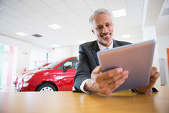 Smiling businessman using tablet at his desk Stock Image