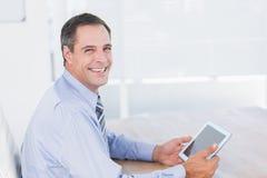 Smiling businessman using tablet Stock Photos