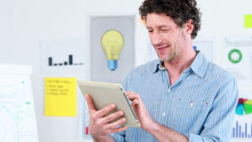 Smiling businessman using a tablet. Portrait of a smiling businessman using a tablet at office stock video