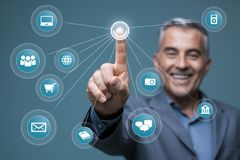 Smiling businessman using a virtual interface. With app icons, he is accessing a virtual dashboard and networking on a visual screen Stock Photography