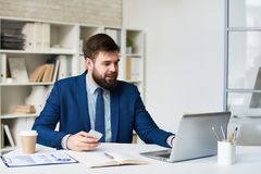 Smiling Businessman in Video Call Meeting. Portrait of young bearded businessman smiling while having video call meeting at desk in office Stock Image