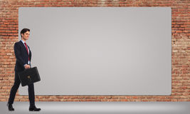 Smiling businessman  walking by a big billboard Royalty Free Stock Image