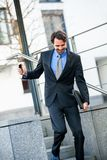 Smiling businessman walking down stairs Stock Image