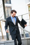 Smiling businessman walking down stairs Royalty Free Stock Photos
