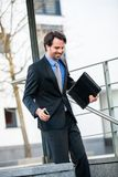 Smiling businessman walking down stairs royalty free stock images