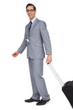 Smiling businessman walking with his suitcase Royalty Free Stock Photography