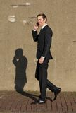 Smiling businessman walking and talking on cellphone Royalty Free Stock Image